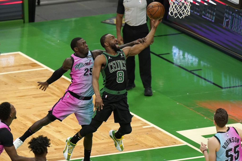 Boston Celtics' Kemba Walker (8) drives toward the basket as Miami Heat's Kendrick Nunn (25) tries to block in the second half of a basketball game, S...
