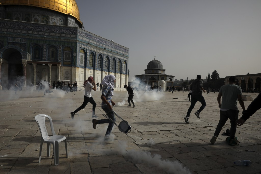 Palestinians run away from tear gas during clashes with Israeli security forces at the Al Aqsa Mosque compound in Jerusalem's Old City Monday, May 10,...