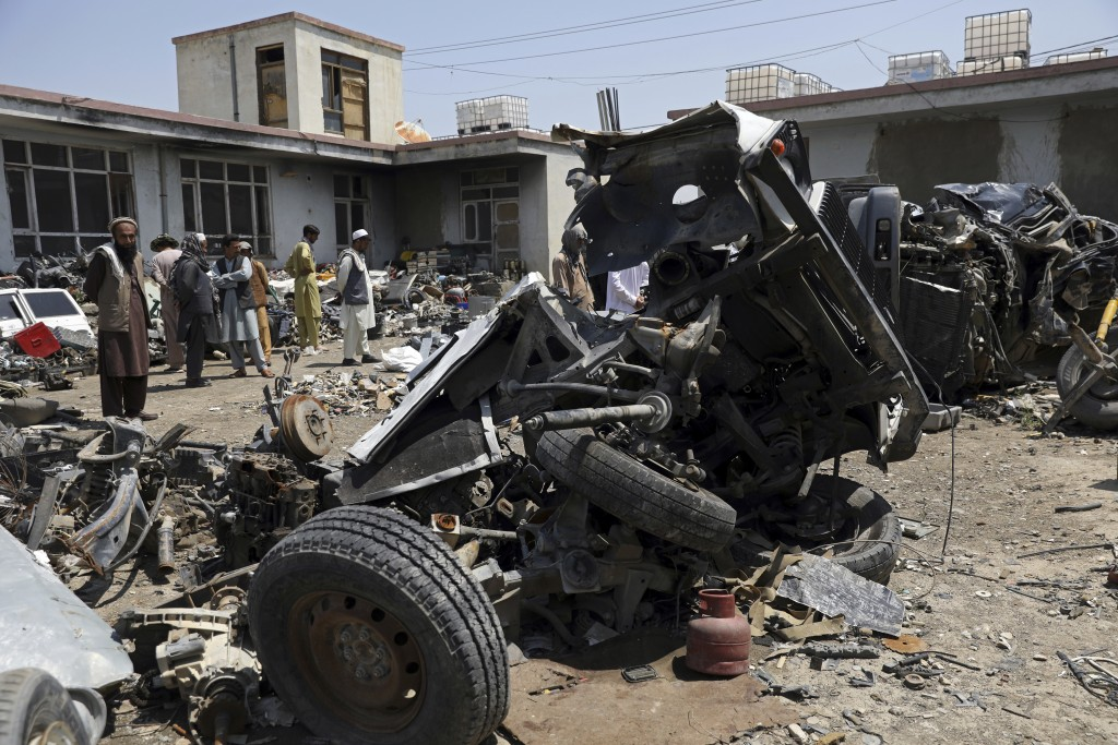 Afghans stand inside Baba Mir's scrapyard outside Bagram Air Base, northwest of the capital Kabul, Afghanistan, Monday, May 3, 2021. As US troops pack...