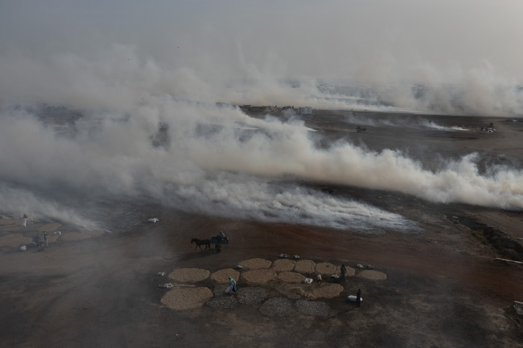 Plumes of smoke from fish processing rise above Bargny beach, some 35 kilometers (22 miles) east of Dakar, Senegal, Wednesday April 21, 2021. In Bargn...