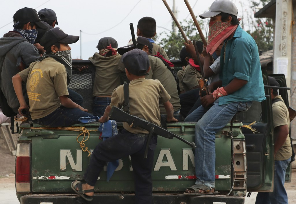 Children, some carrying real weapons and others with fake ones, patrol their community aboard a pick-up truck as part of a display by community leader...