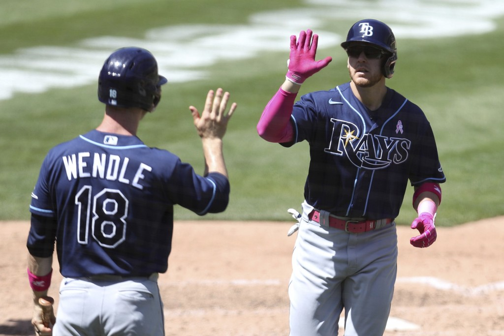 Tampa Bay Rays' Mike Brosseau, right, is congratulated by teammate Joey Wendle after hitting a solo home run against the Oakland Athletics during the ...