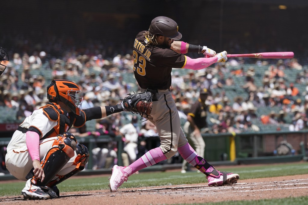 San Diego Padres' Fernando Tatis Jr., right, hits a two-run home run in front of San Francisco Giants catcher Buster Posey during the second inning of...