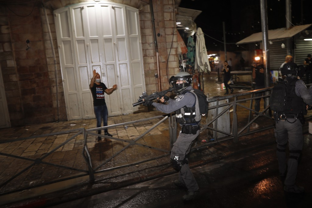 Israeli police officers aims his rifle during clashes with Palestinians near Damascus Gate just outside Jerusalem's Old City, Sunday, May 9, 2021. Isr...