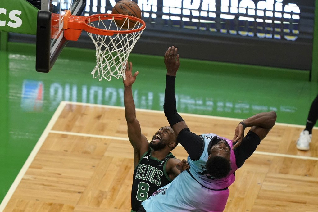 Boston Celtics' Kemba Walker, left, shoots at the basket as Miami Heat's Bam Adebayo, right, tries to block in the first half of a basketball game, Su...