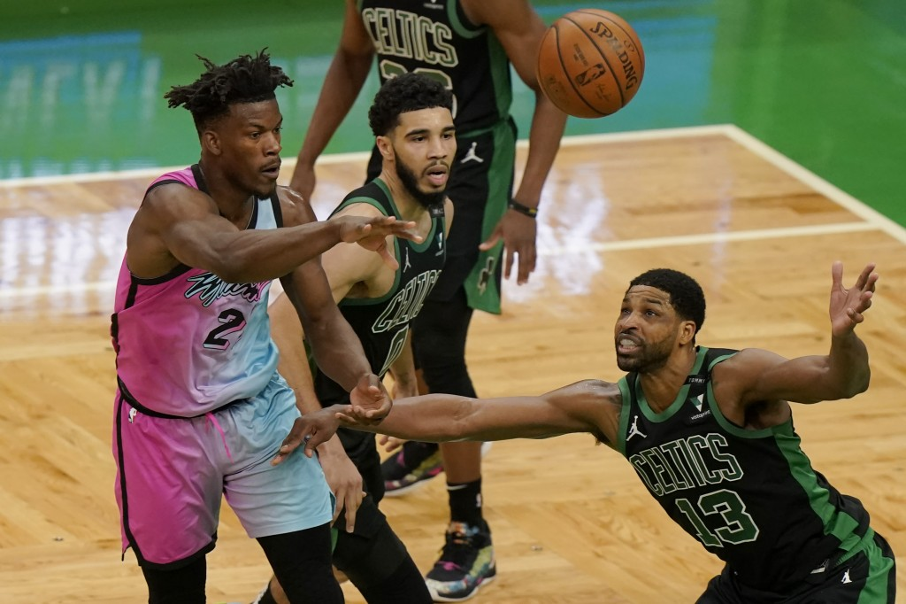 Miami Heat's Gabe Vincent, left, passes the ball as Boston Celtics' Jayson Tatum, center, and Tristan Thompson, right, try to block in the first half ...