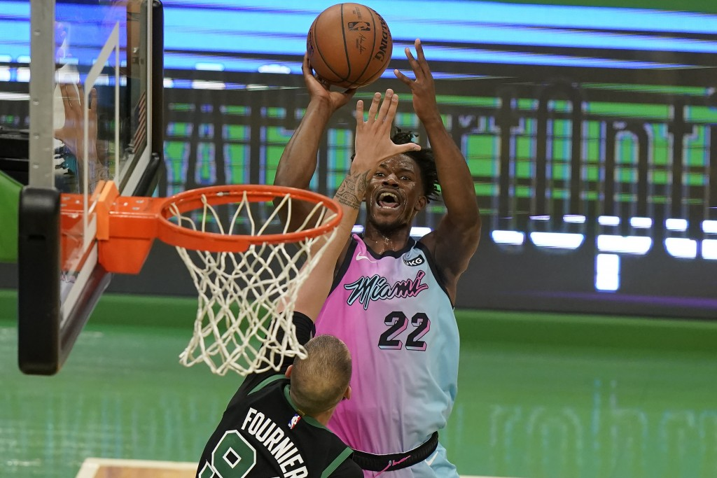 Miami Heat's Jimmy Butler (22) shoots at the basket as Boston Celtics' Evan Fournier (94) tries to block in the second half of a basketball game, Sund...