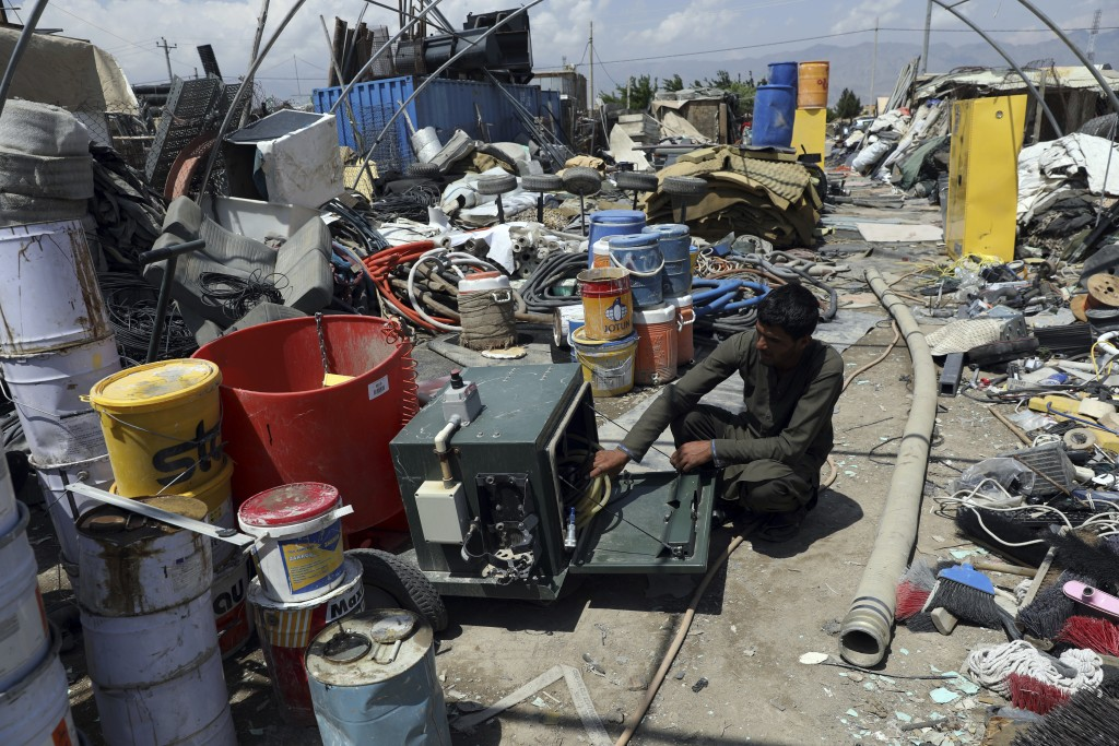 A scrap dealer checks equipment in a scrapyard outside Bagram Air Base, northwest of the capital Kabul, Afghanistan, Monday, May 3, 2021. As US troops...
