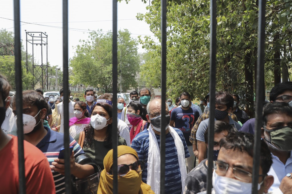 People waiting to get vaccinated against the coronavirus stand outside the closed gates of a hospital in Ghaziabad, outskirts of New Delhi, India, Mon...