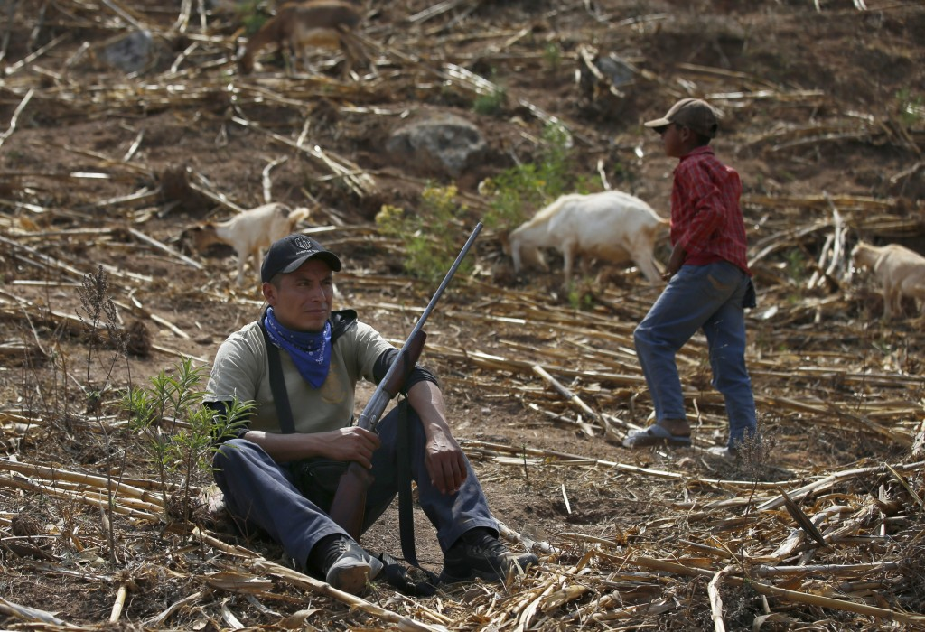Community policeman Silvano Martinez guards his 11-year-old nephew Geovanni Martinez as he observes his goats in a pasture outside Ayahualtempa, a tow...