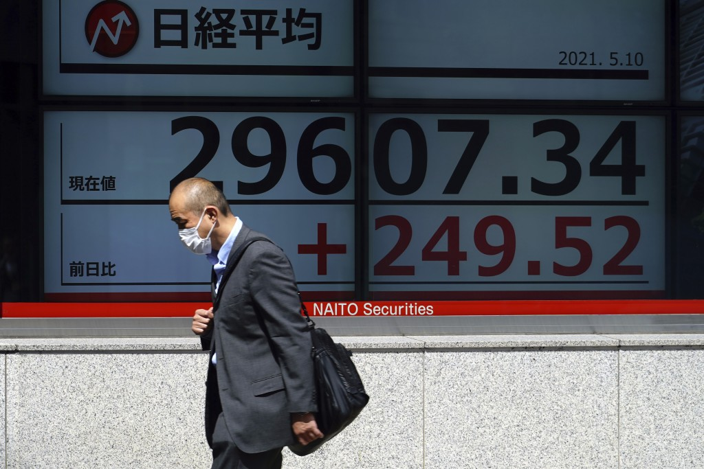 A man wearing a protective mask walks in front of an electronic stock board showing Japan's Nikkei 225 index at a securities firm Monday, May 10, 2021...