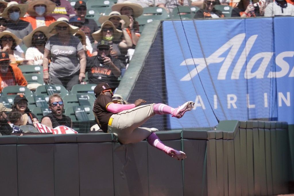 San Diego Padres left fielder Jurickson Profar hits the wall in foul territory after catching a foul out hit by San Francisco Giants' Brandon Crawford...