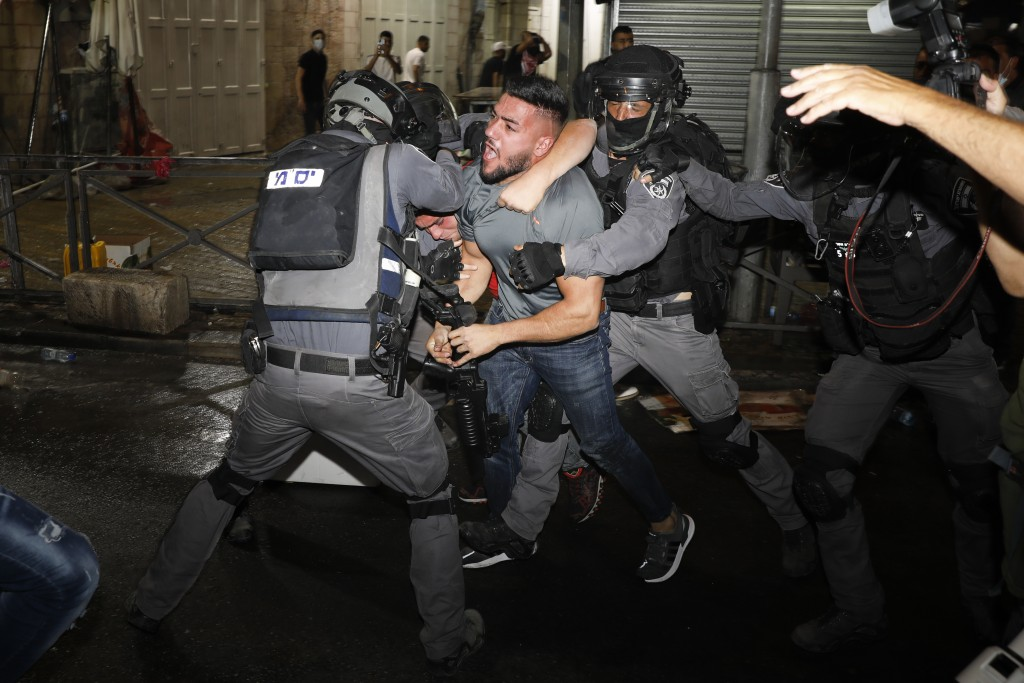 Israeli police officers clash with Palestinian protesters near Damascus Gate just outside Jerusalem's Old City, Sunday, May 9, 2021. (AP Photo/Ariel S...