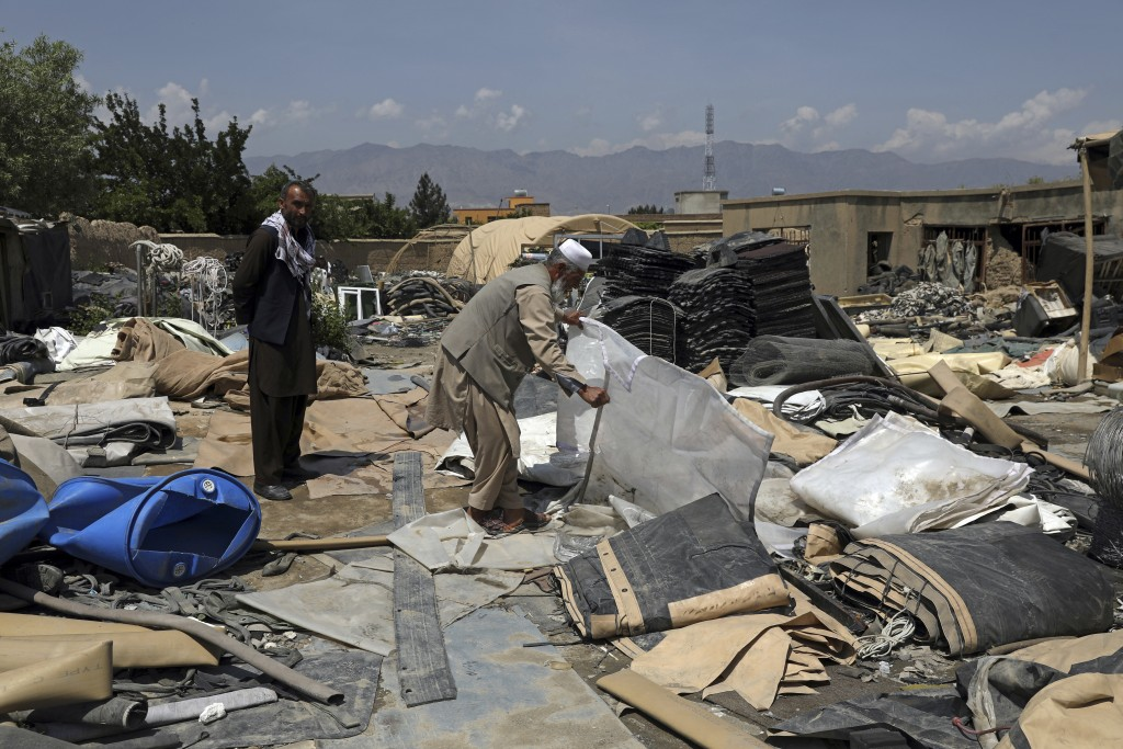 Afghan men sort through piles of tents reduced to sliced up fabric, in a scrapyard outside Bagram Air Base, northwest of the capital Kabul, Afghanista...