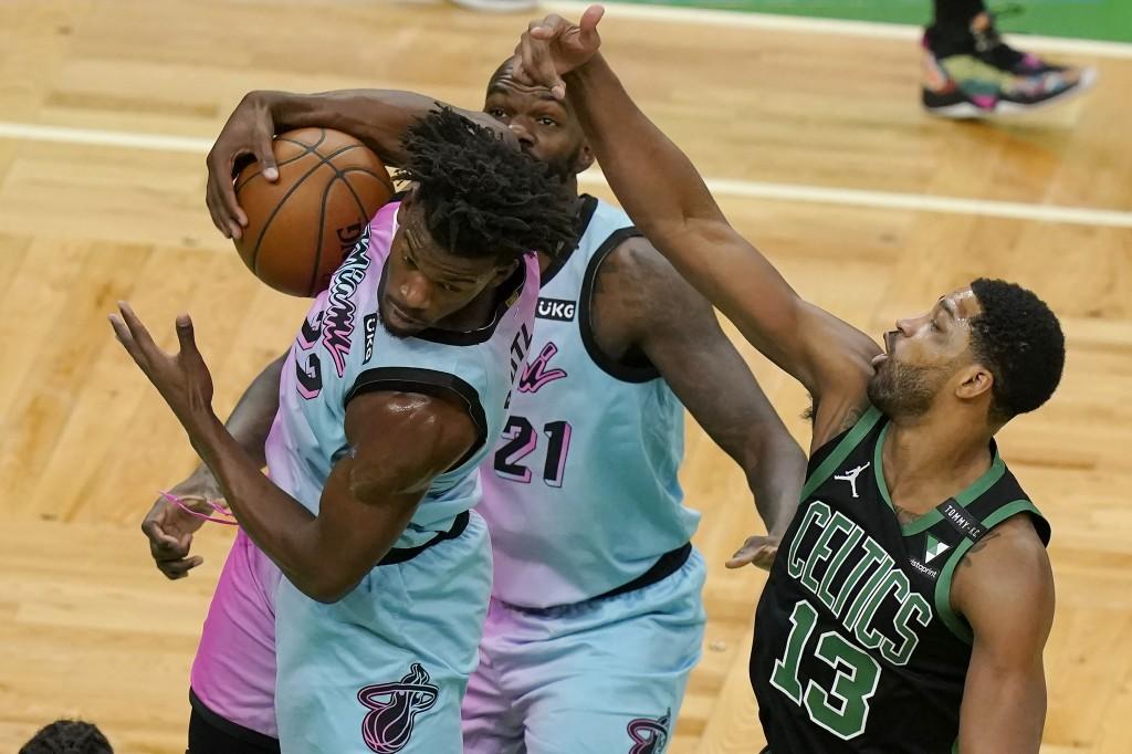 Miami Heat's Jimmy Butler, left, grabs a rebound as Boston Celtics' Tristan Thompson, right, vies for the ball while Heat's Dewayne Dedmon, behind, lo...