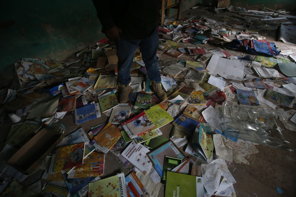 A man stands on textbooks strewn about the floor of a school that has an exterior still pocked with bullet holes in the ghost village of Paraiso de Te...