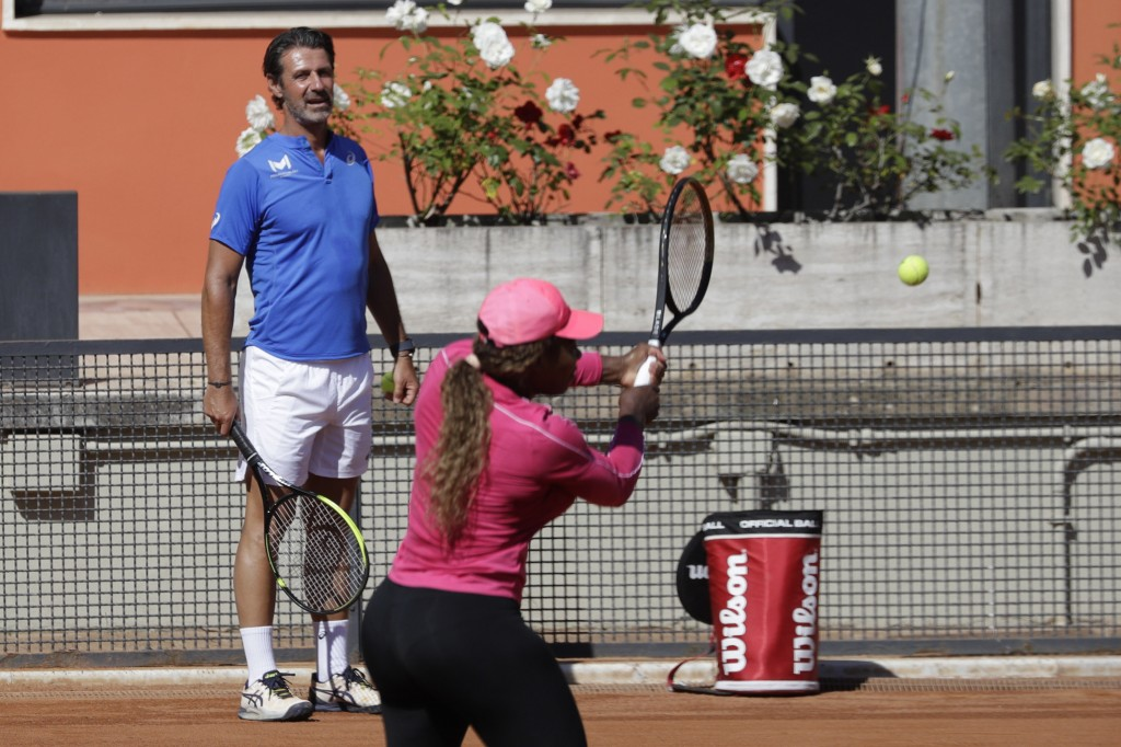Serena Williams returns the ball as her coach Patrick Mouratoglou, left, watches her during a training session at the Italian Open tennis tournament, ...