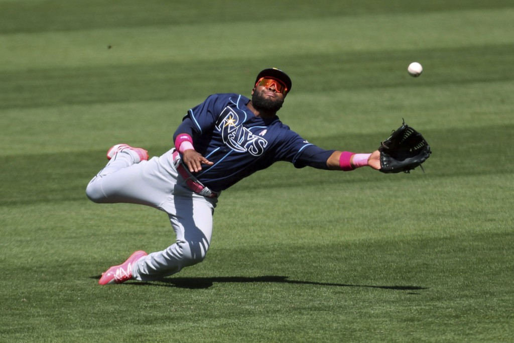 Tampa Bay Rays' Manuel Margot dives for a triple hit by Oakland Athletics' Elvis Andrus during the seventh inning of a baseball game in Oakland, Calif...