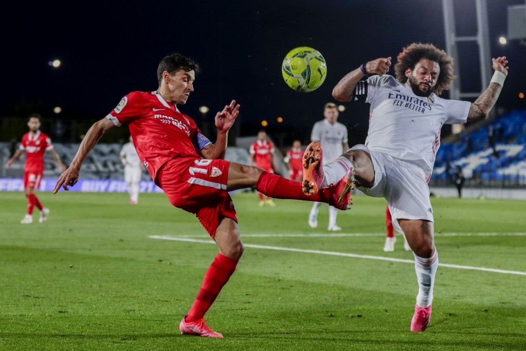 Sevilla's Jesus Navas, left, vies for the ball with Real Madrid's Marcelo during the Spanish La Liga soccer match between Real Madrid and Sevilla at t...