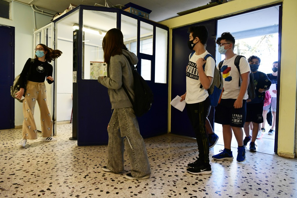 Students wearing face masks to help curb the spread of the coronavirus, wait to check their temperature at a junior high school in Athens, Monday, May...