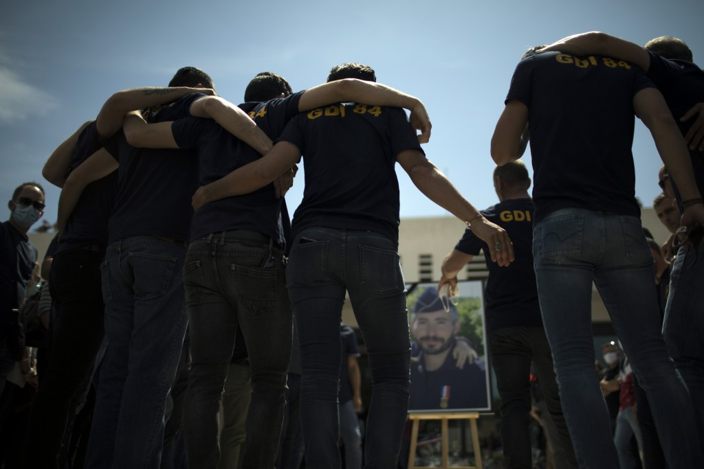 Police officers console each other during a ceremony to commemorate a slain colleague at a police station in Avignon, southern France, Sunday, May 9, ...