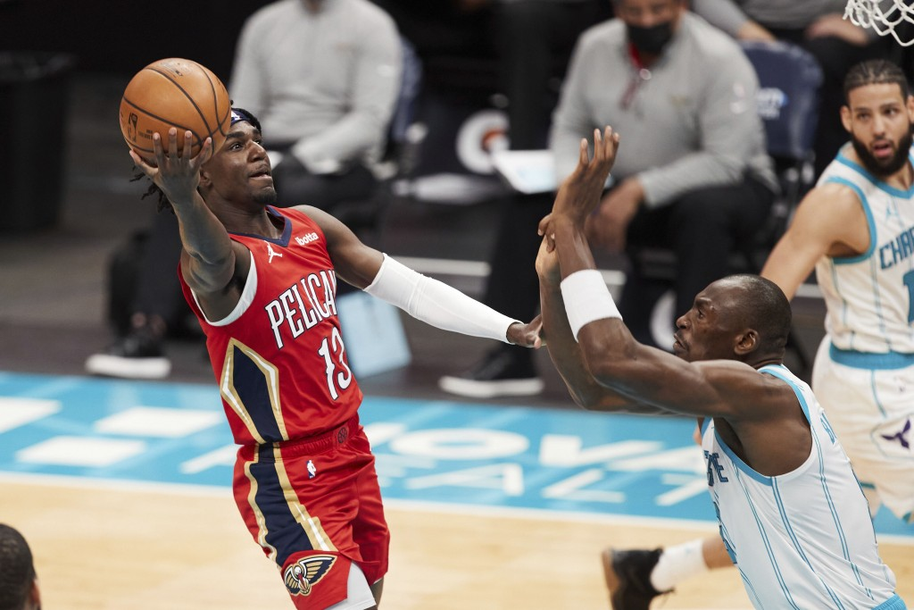 New Orleans Pelicans guard Kira Lewis Jr. (13) looks to shoot over Charlotte Hornets center Bismark Biyombo during the first half of an NBA basketball...