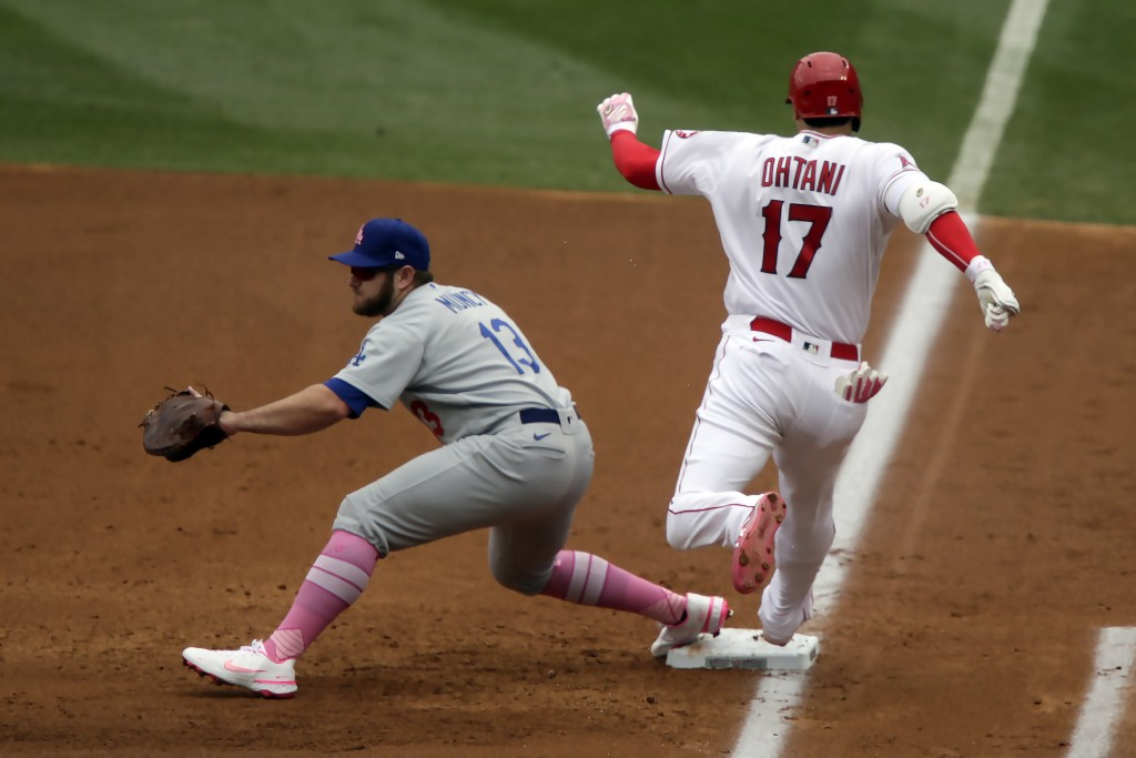 Los Angeles Angels designated hitter Shohei Ohtani, right, beats the throw to Los Angeles Dodgers first baseman Max Muncy for an infield single during...