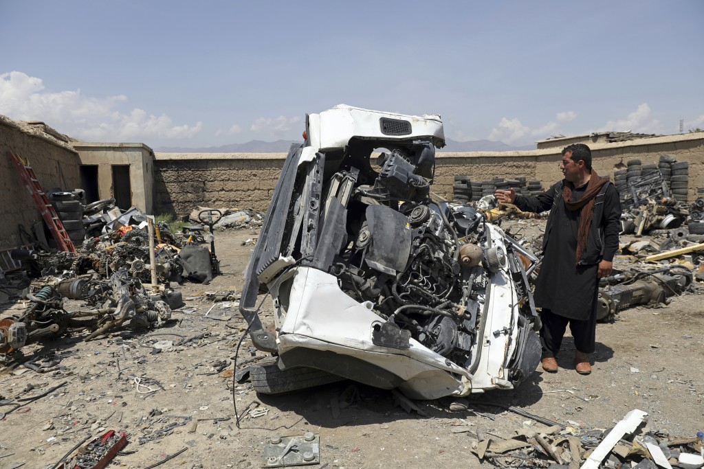 An Afghan man looks at a damaged vehicles in Baba Mir's scrapyard outside Bagram Air Base, northwest of the capital Kabul, Afghanistan, Monday, May 3,...