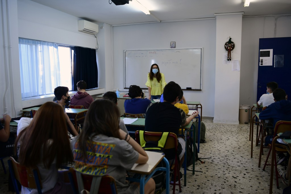 A teacher wearing a face mask to help curb the spread of the coronavirus, welcomes her students at a junior high school class in Athens, Monday, May 1...