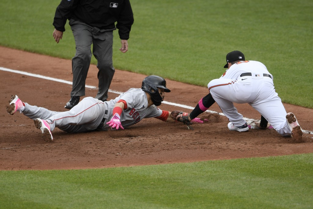 Boston Red Sox's Marwin Gonzalez, front left, is tagged out by Baltimore Orioles first baseman Ryan Mountcastle, right, on a pickoff during the third ...