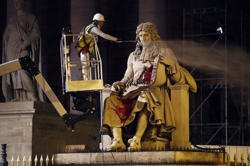 FILE - In this June 23, 2020 file photo, a worker from Paris' City Hall cleans the statue of Jean-Baptiste Colbert, in Paris. Trial began on Monday fo...