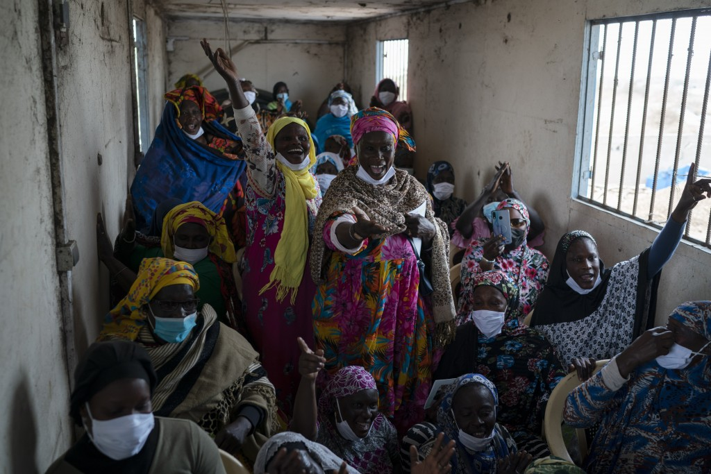Siny Gueye, center left, is joined by other women fish processors to sing a blessing and thankful song at Bargny beach, some 35 kilometers (22 miles) ...