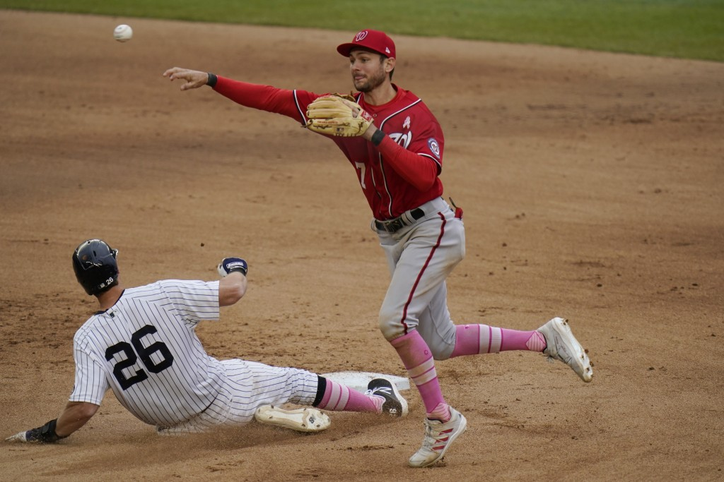 Washington Nationals shortstop Trea Turner, right, turns a double play over New York Yankees' DJ LeMahieu during the seventh inning of a baseball game...