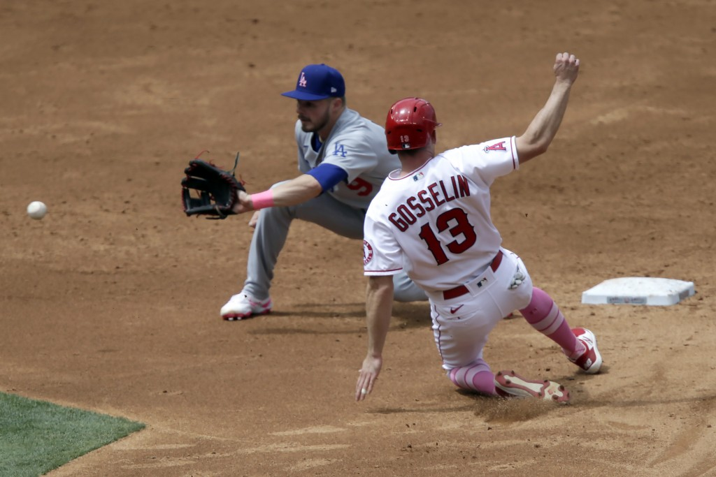 Los Angeles Dodgers second baseman Gavin Lux, left, waits for the throw before tagging out Los Angeles Angels' Phil Gosselin on a steal attempt during...