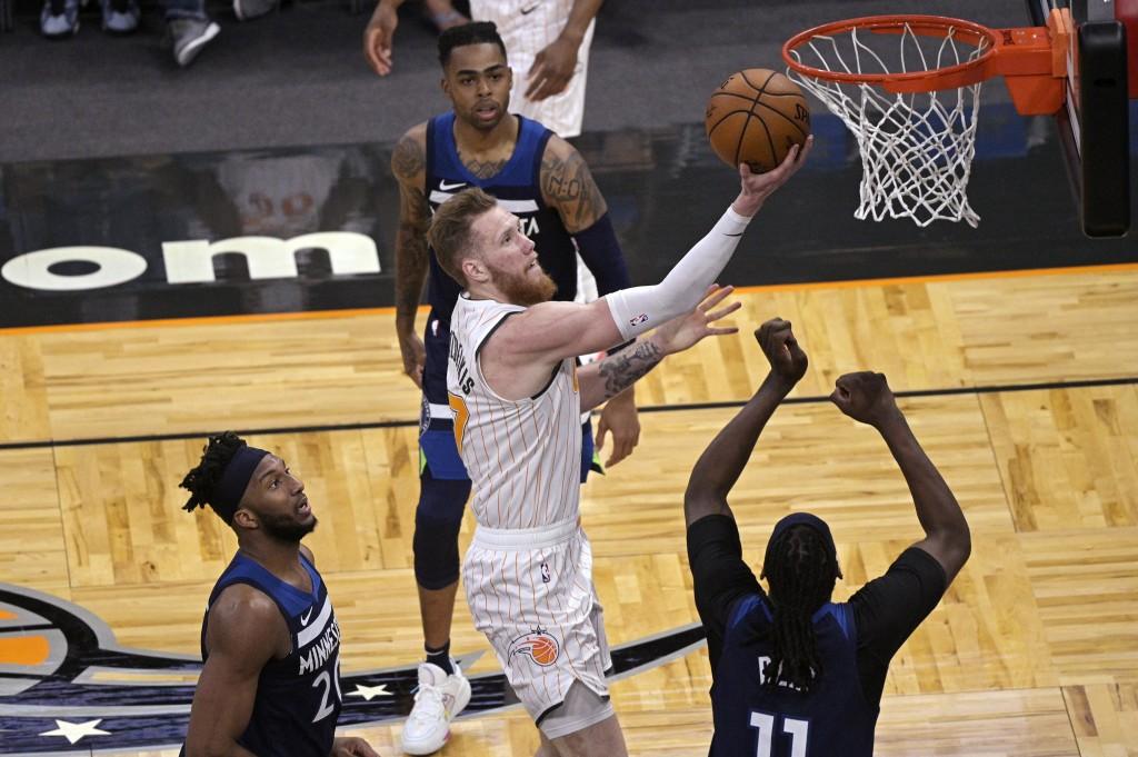 Orlando Magic forward Ignas Brazdeikis (17) shoots between Minnesota Timberwolves forward Josh Okogie (20), guard D'Angelo Russell, rear, and center N...