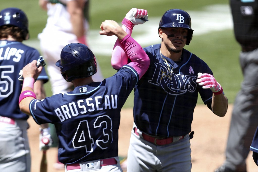 Tampa Bay Rays' Willy Adames, right, is congratulated by teammate Mike Brosseau after hitting a three-run home run against the Oakland Athletics durin...