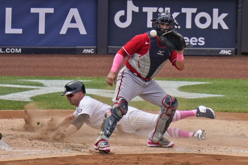 Washington Nationals catcher Yan Gomes, front, waits for the ball while New York Yankees' Brett Gardner slides safely home during the third inning of ...