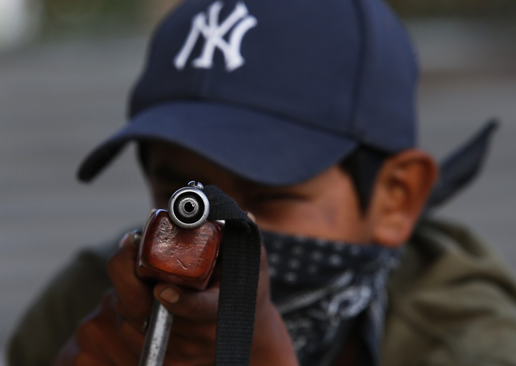 Luis Gustavo Morales, the 15-year-old son of a community policeman, practices his aim with a fake weapon during a display set up for the media to attr...