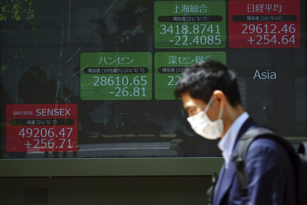 A man wearing a protective mask rides a bicycle in front of an electronic stock board showing Japan's Nikkei 225 and other Asian indexes at a securiti...