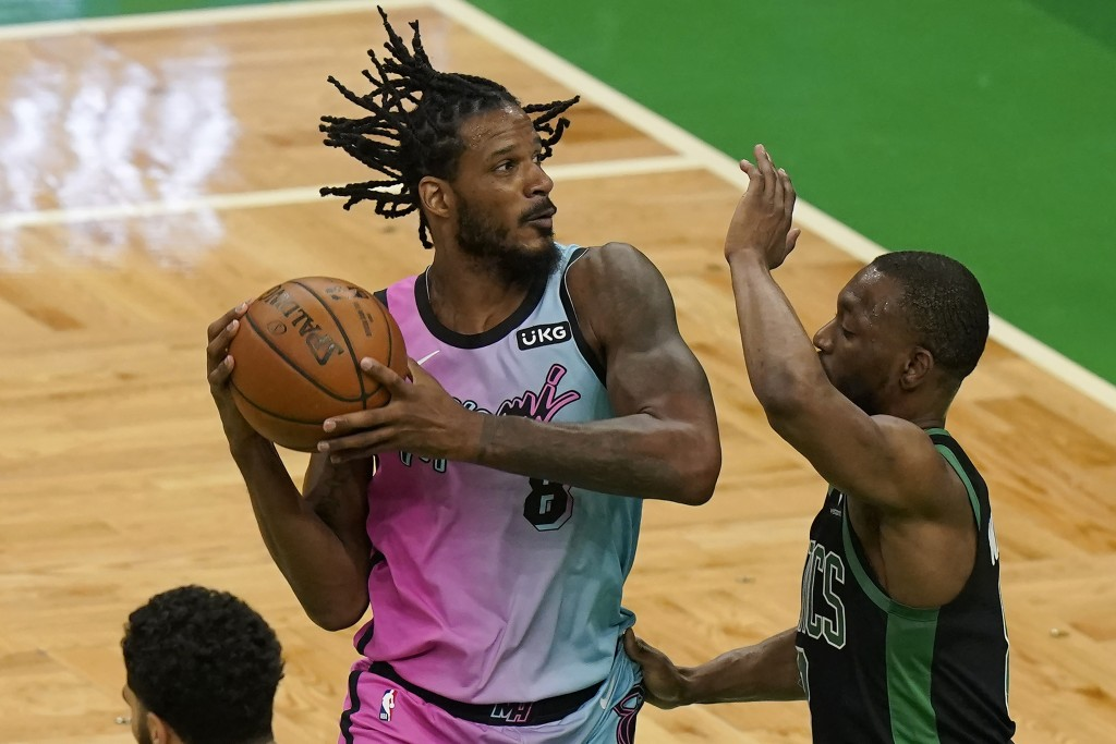 Miami Heat's Trevor Ariza, left, looks for an opening as Boston Celtics' Kemba Walker (8) tries to block in the first half of a basketball game, Sunda...