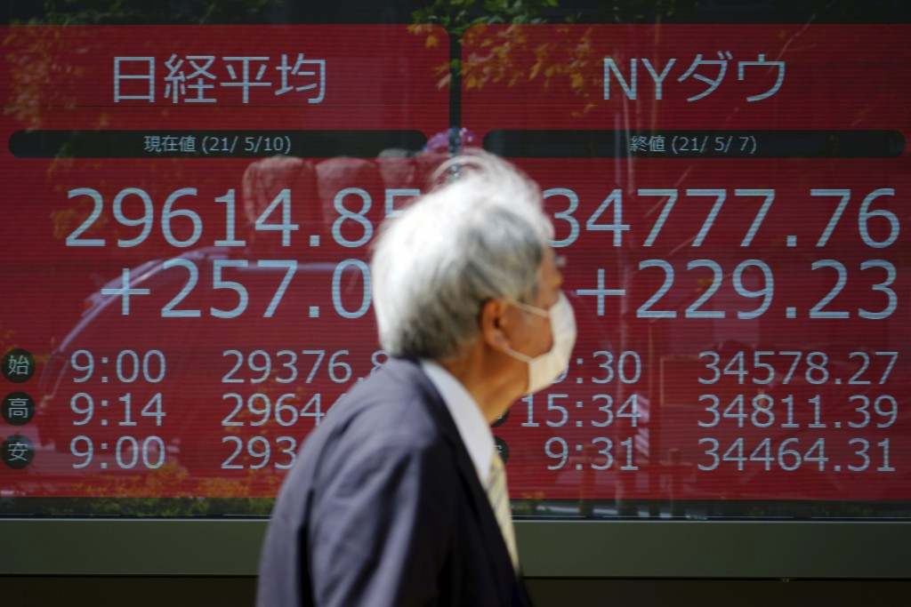 A man wearing a protective mask walks in front of an electronic stock board showing Japan's Nikkei 225 and New York Dow index at a securities firm Mon...
