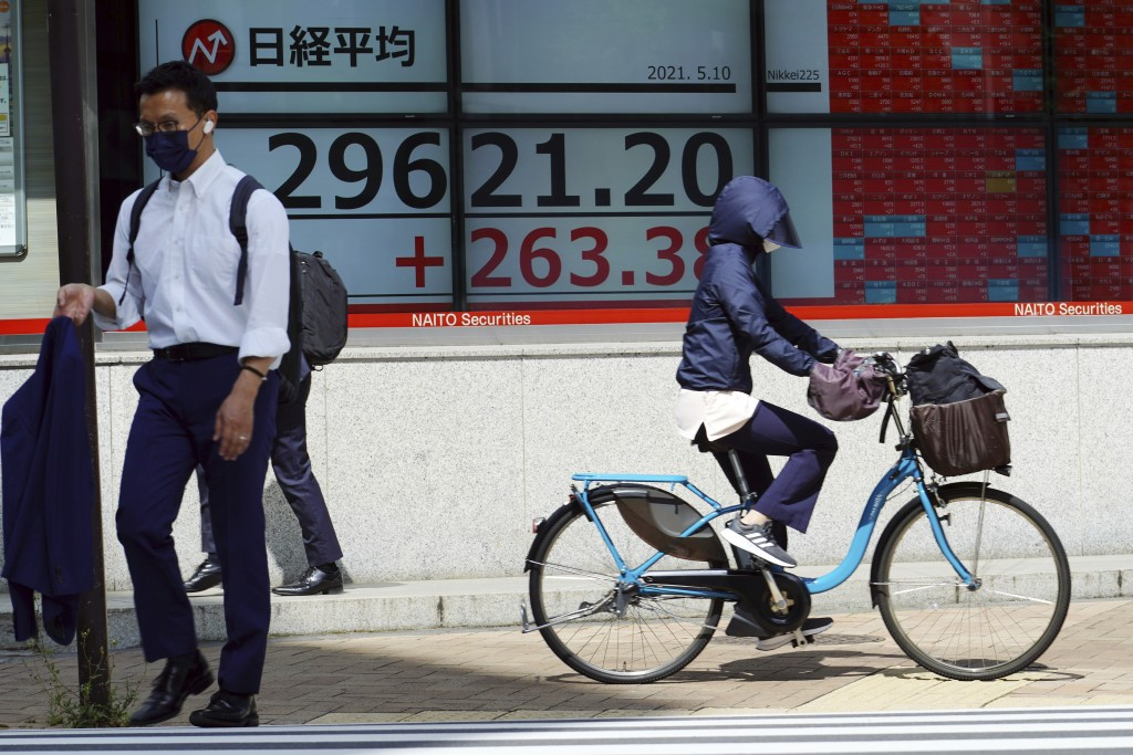 A woman wearing a protective mask rides a bicycle in front of an electronic stock board showing Japan's Nikkei 225 index at a securities firm Monday, ...