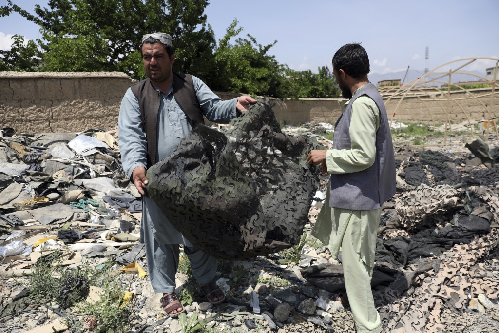Afghan men hold scraps of tenting at a scrapyard outside Bagram Air Base, northwest of the capital Kabul, Afghanistan, Monday, May 3, 2021. As US troo...