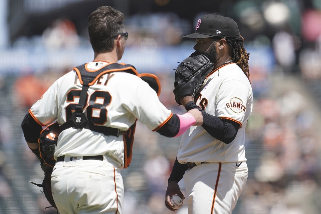 San Francisco Giants pitcher Johnny Cueto, right, stands on the mound as catcher Buster Posey (28) approaches during the third inning of a baseball ga...