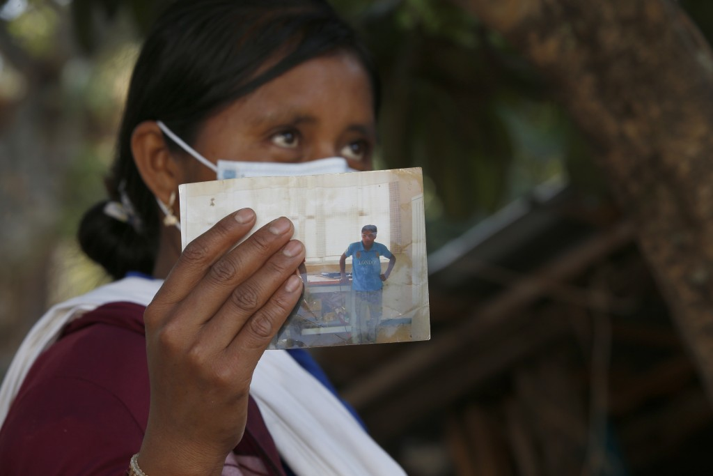 Basilia Tepetitlan holds a photo of her husband who was murdered along with nine other musicians including a 15-year-old boy by a criminal gang that b...