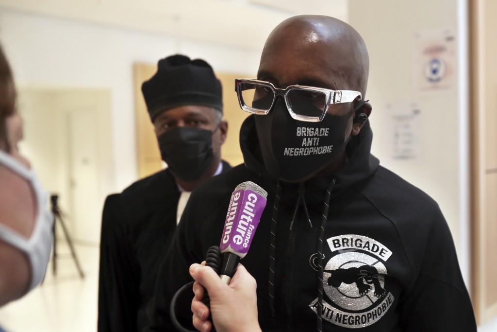 An activist from a group called the Anti-Negrophobia Brigade, Franco Lollia, wears a face mask reading «Anti-Negrophobia Brigade» as he talks to med...