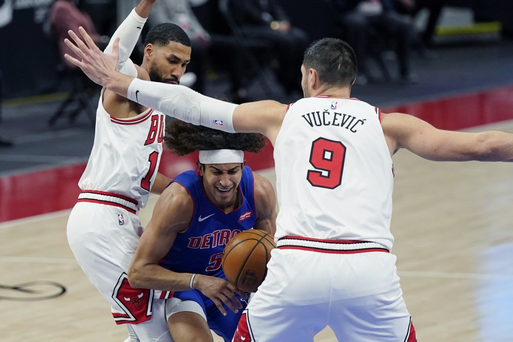 Detroit Pistons guard Frank Jackson (5) is defended by Chicago Bulls forward Garrett Temple (17) and center Nikola Vucevic (9) during the first half o...