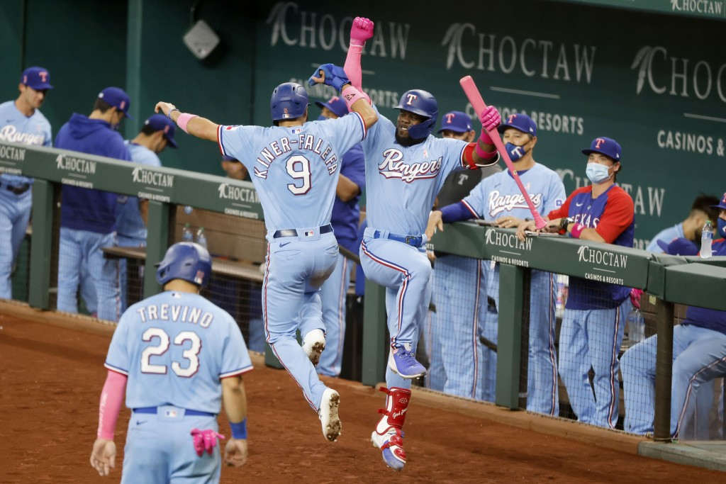 Texas Rangers Isiah Kiner-Falefa (9) celebrates with Adolis Garcia, right, after scoring on a double by Willie Calhoun during the fifth inning of a ba...