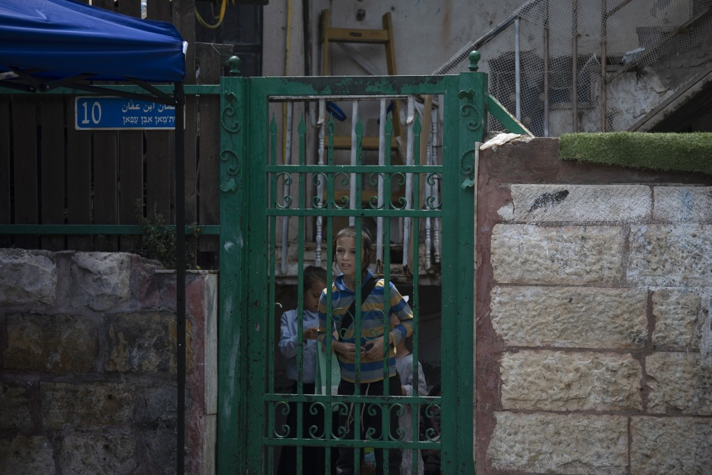 A child peers from the front gate of a Palestinian house occupied by Israeli settlers, days ahead of a court verdict that may forcibly evict Palestini...