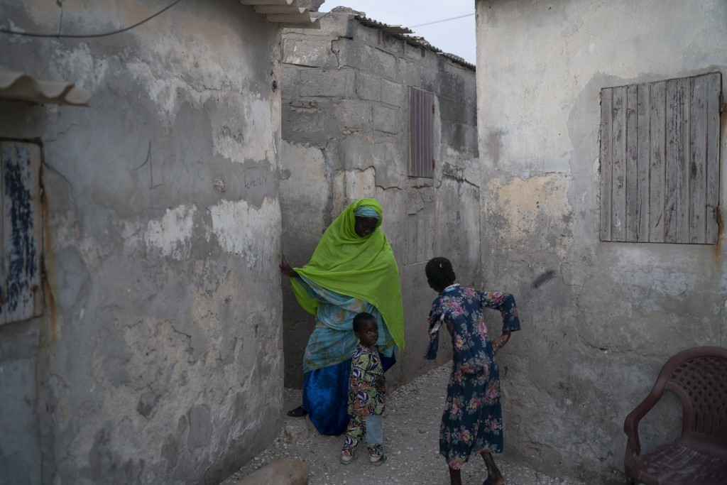 Ndeye Yacine Dieng talks with her 3-year-old grandson Babacar as she arrives at her home in Bargny, Senegal some 35 kilometers (22 miles) east of Daka...